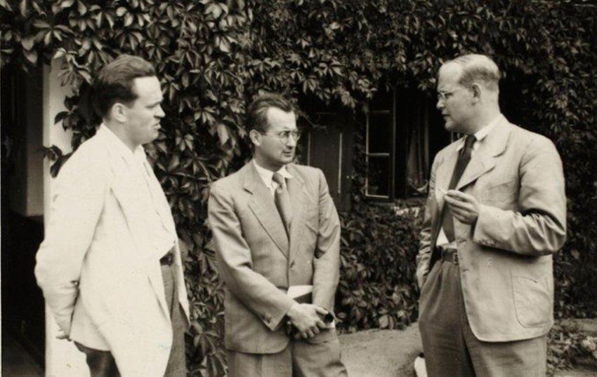 Dietrich Bonhoeffer (r.) mit Zigarette in der Hand, neben ihm stehen Eberhard Bethge (l.) und Hellmut Traub (M.). Aufgenommen wurde das Foto im August 1939 vor dem Jagdhaus Sigurdshof bei Groß-Schlönwitz