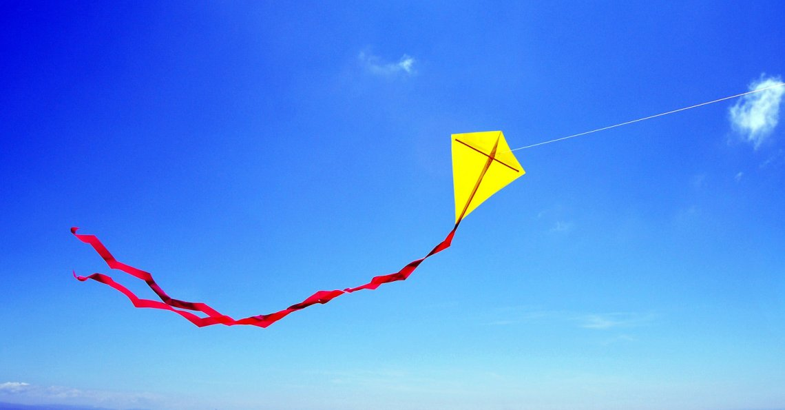 yellow-kite-flying-in-the-shape-of-a-cross